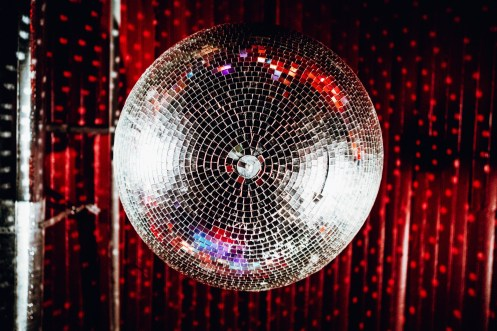 Above the crowd, a disco ball spins and casts tiles of light over performers and patrons at a bar in Nashville, TN.