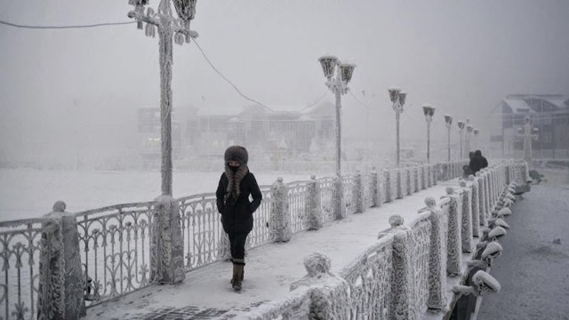 A-woman-walks-over-an-ice-encrusted-bridge-in-Yakutsk.-Oymyakon-lies-a-two-day-drive-from-the-city-of-Yakutsk-the-regional-capital-Welcome-to-The-Coldest-Place-Inhabited-By-Humans-on-Earth