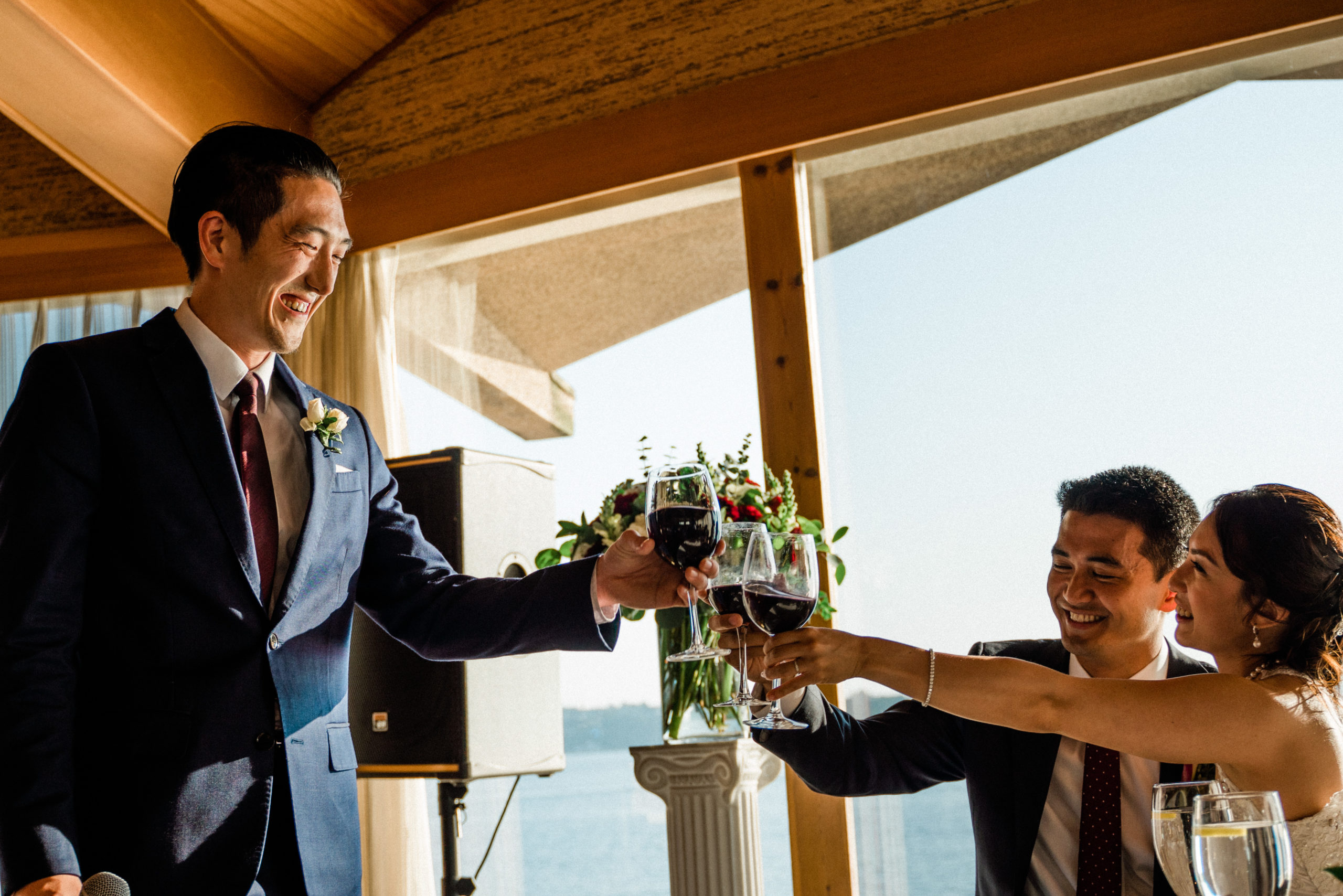 best man cheers a wine glass at ballroom site on edgewater hotel