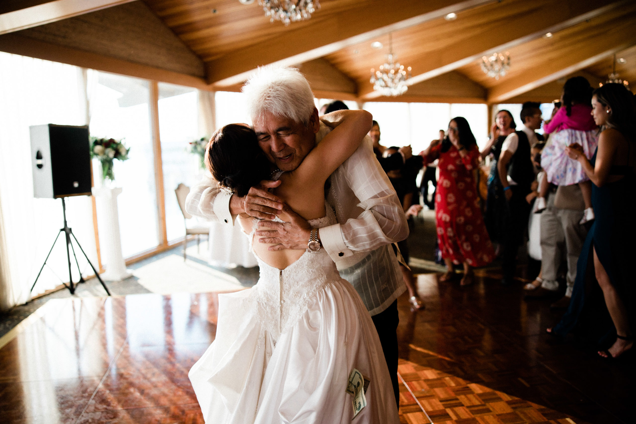 father hugs his daughter after getting married at edgewater hotel on the seattle waterfront