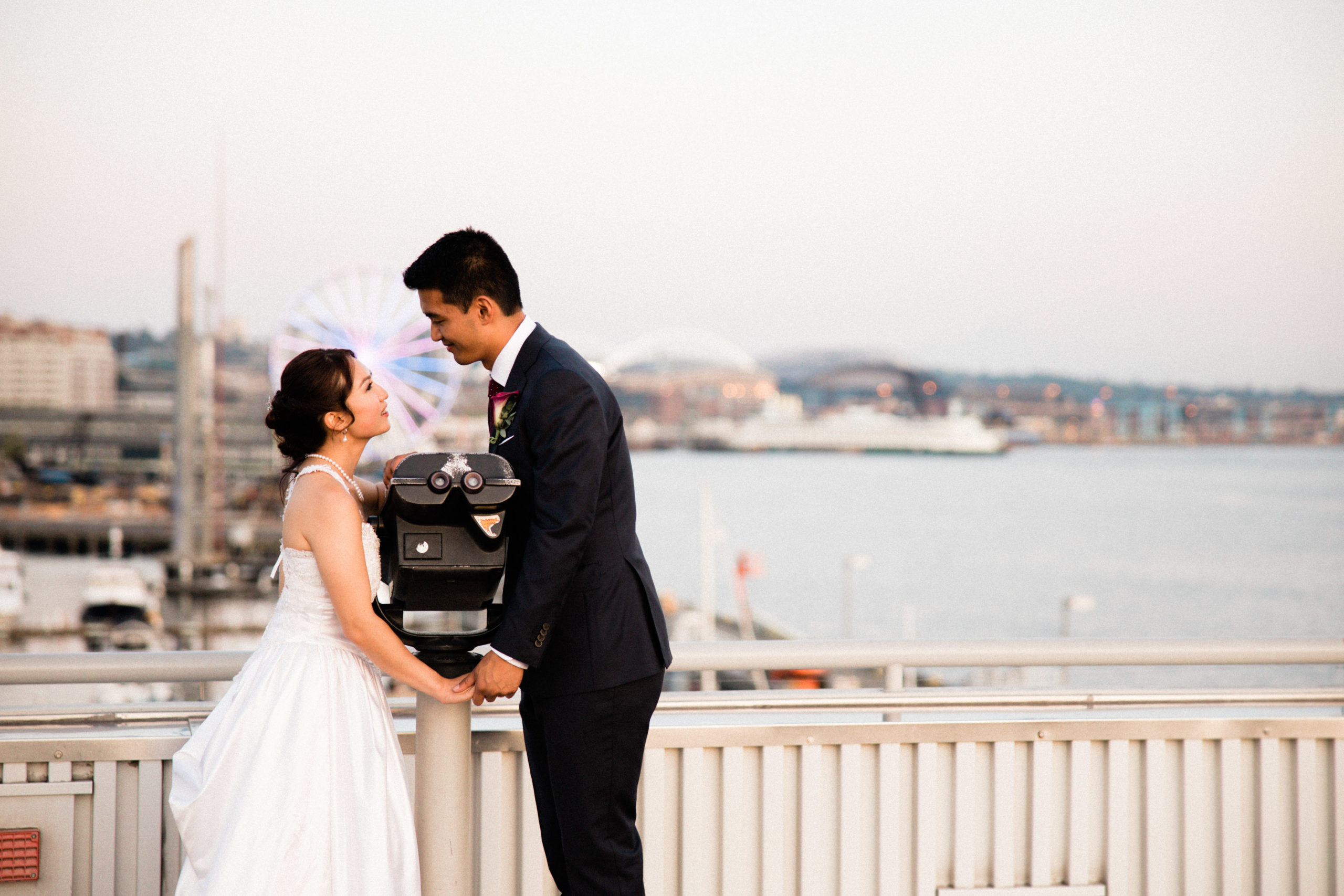 intimate portraits outside edgewater hotel wedding venue with Ferris wheel and buildings in the background