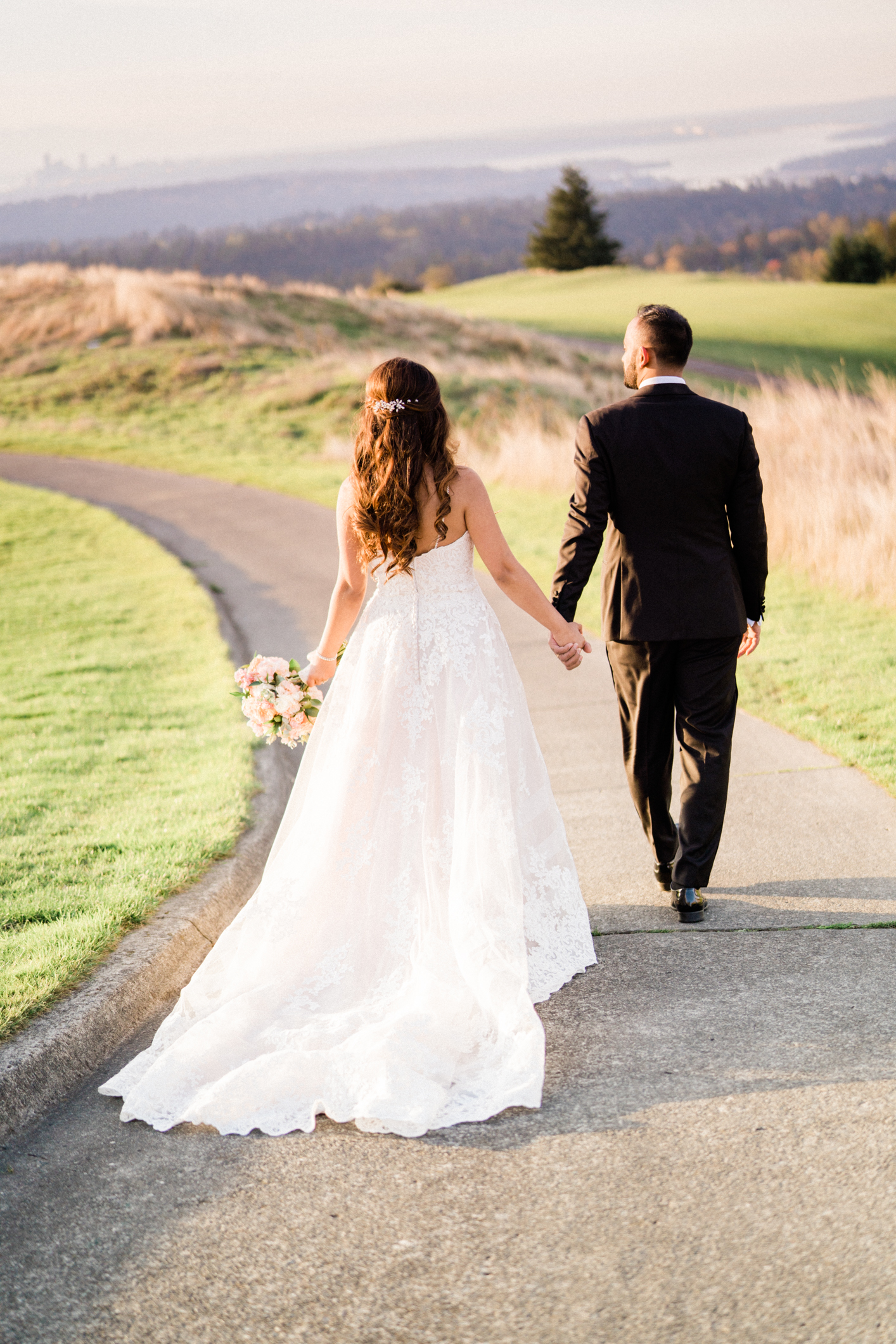 husband and wife hold hands walking on golf course
