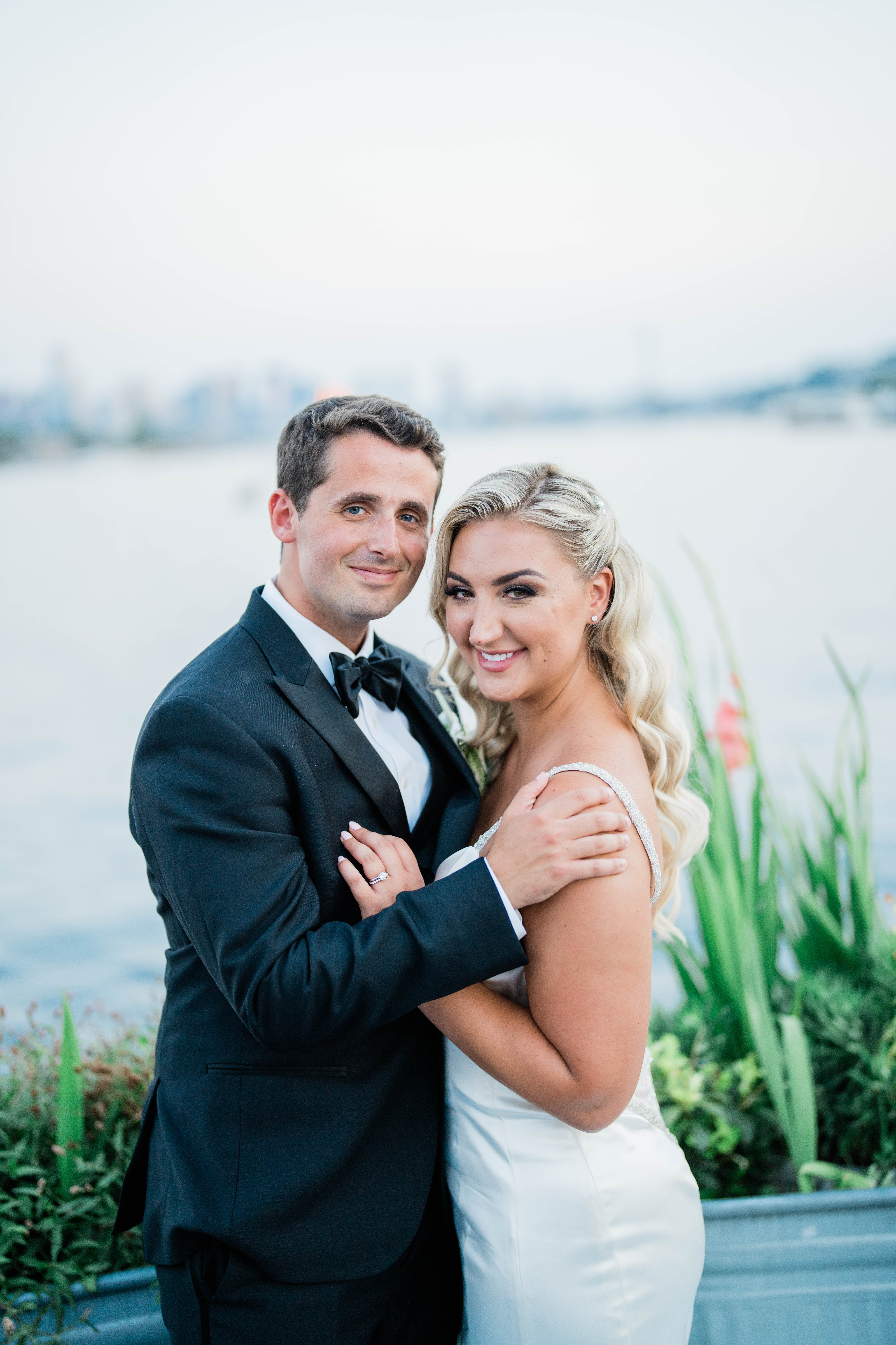 wedding photographer takes couples portraits with seattle skyline