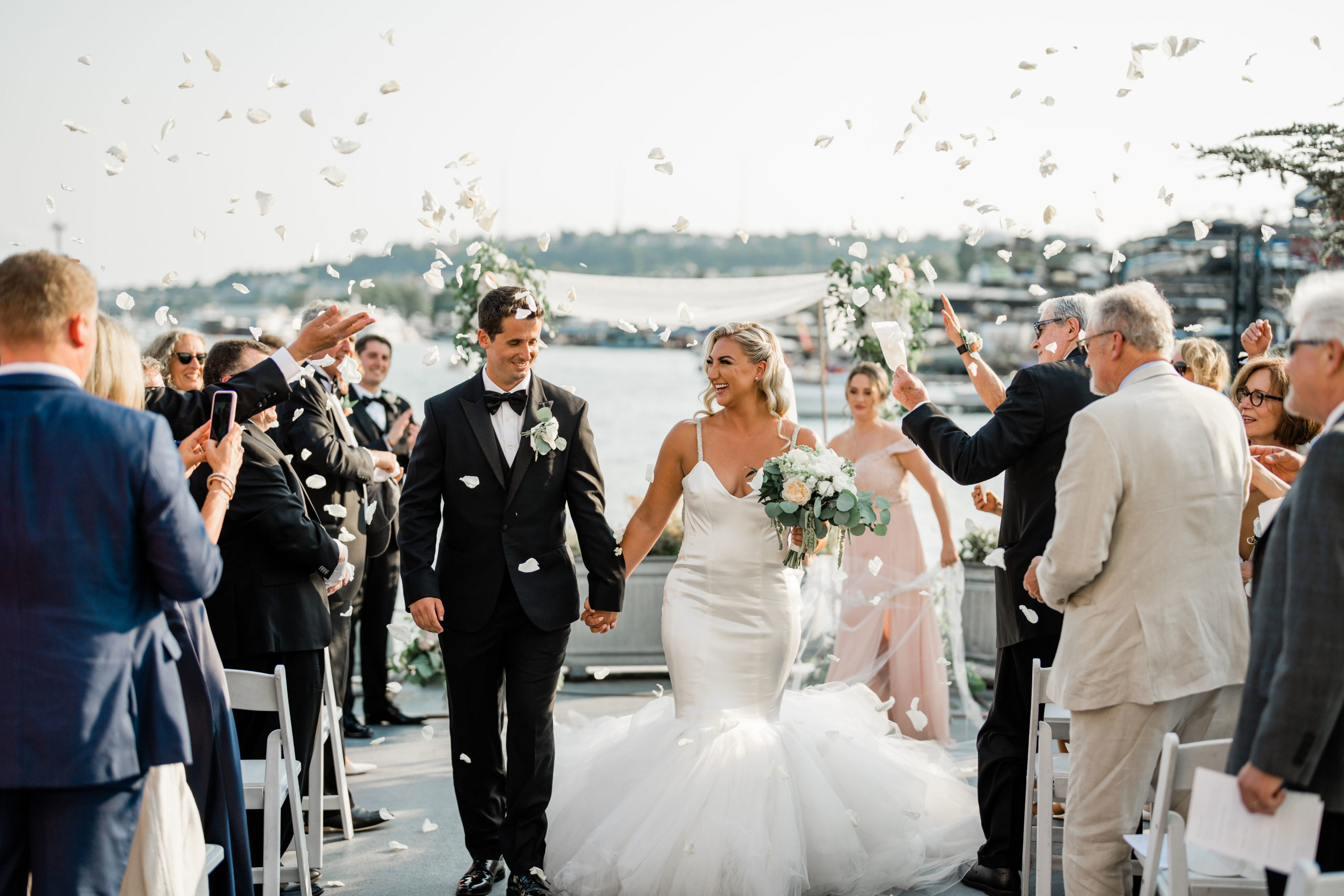 guests throw confetti as husband and wife walk down aisle on MV Skanso