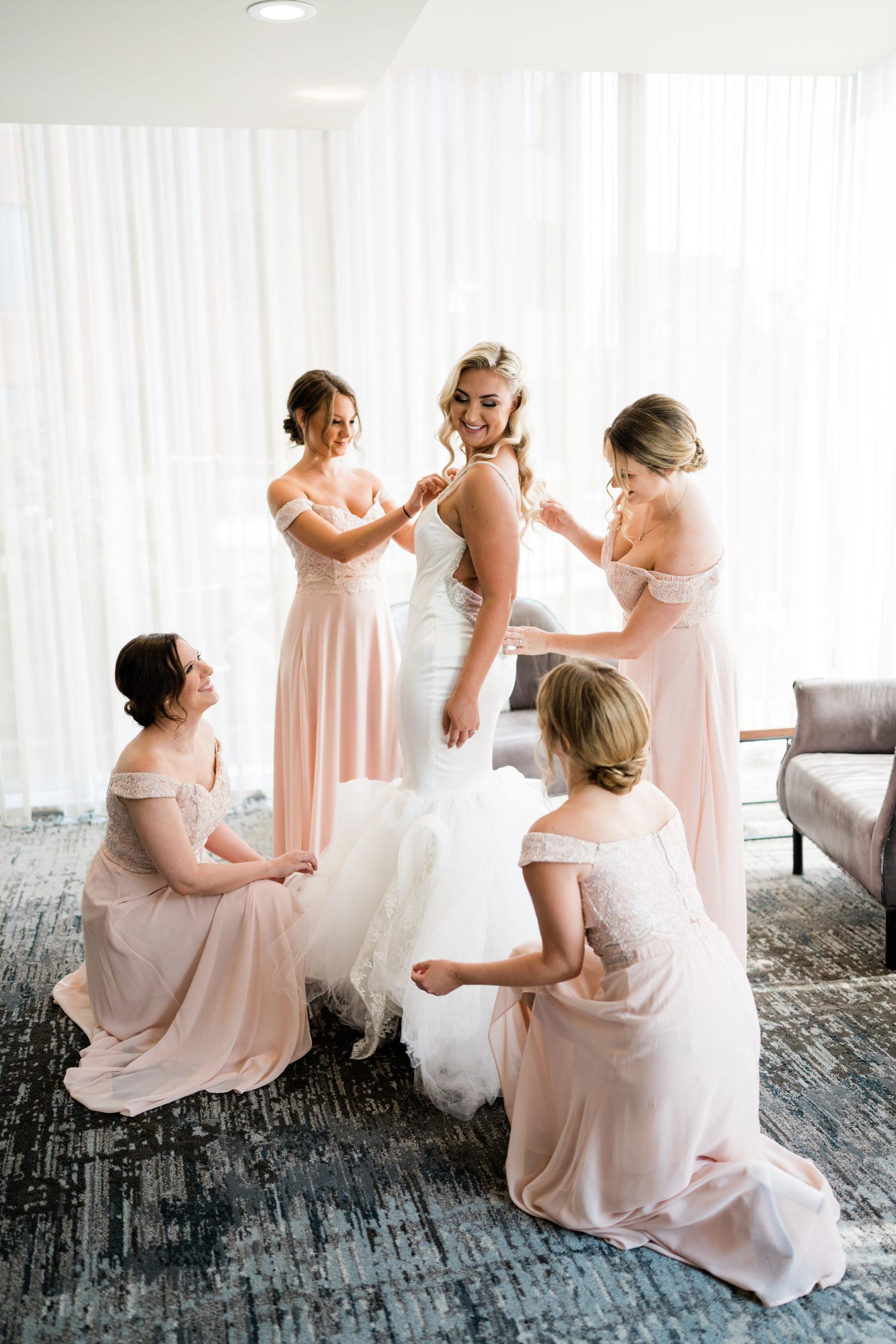 Bridesmaids help bride into her wedding dress before ceremony on MV Skanson