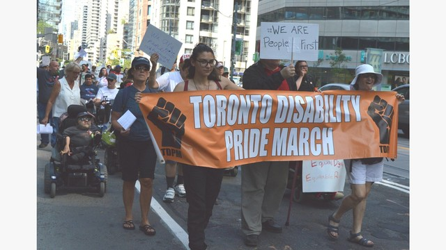 People marching on a street holding signs. Main organge banner says Toronto Disability Pride March and there is a fist on each side of the banner.