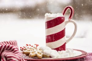 Winter scene with a red a white mug of hot chocolate resting on a plate of cookies and marshmallows.