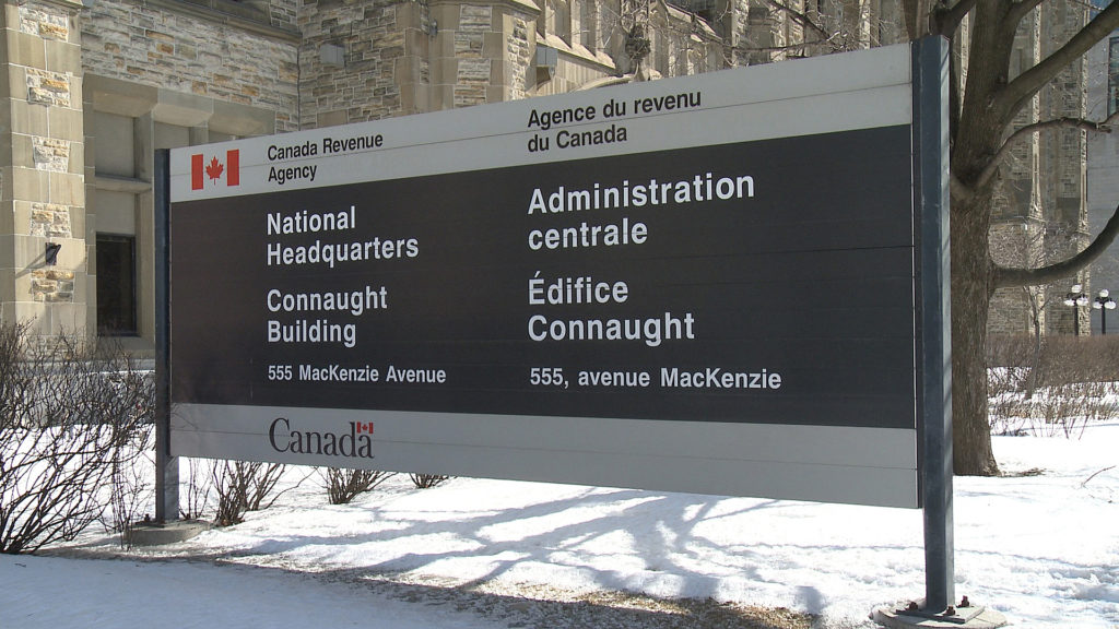 Official outdoor sign on a snowy lawn. Text: Canada Revenue Agency