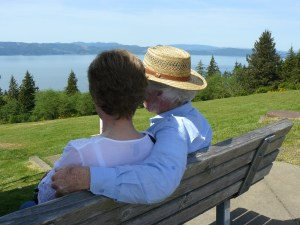 An older man and woman are sitting on a bench thinking about their life together