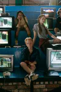 Teens sitting on bleachers next to computer monitors looking bored