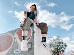 rebellious tattooed lady relaxing in skate park on sunny day. she feels confident in her self-identity.