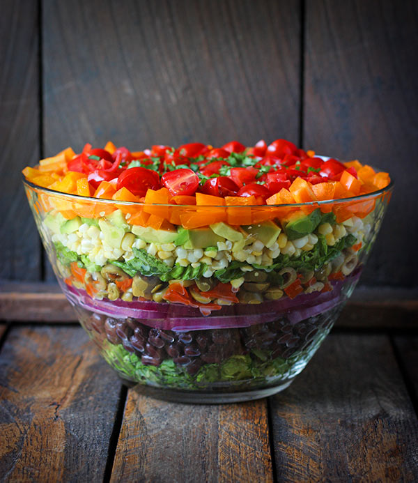 Close up of Seven Layer Salad in a glass bowl on a wooden table