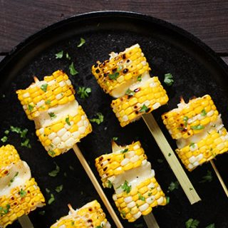 Grilled Corn Kebabs with Salty Cheese - Sweet and crunchy disks of fresh corn sandwich salty, grillable Greek cheese. A great summer party appetizer or side!