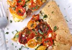 Loaded Heirloom Tomato Galette with Cornmeal Crust from SoupAddict.com - sweet and tangy heirloom cherry tomatoes adorn this veggie-loaded galette, with zucchini, summer squash, leeks, prosciutto, and goat cheese, all on a hearty cornmeal crust.