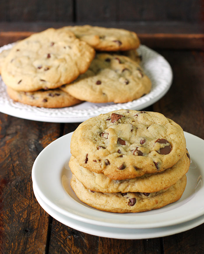 A stack of XXL Soft Baked Chocolate Chip Cookies on a plate.