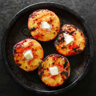 Grilled peaches with a pat of butter, on a tin