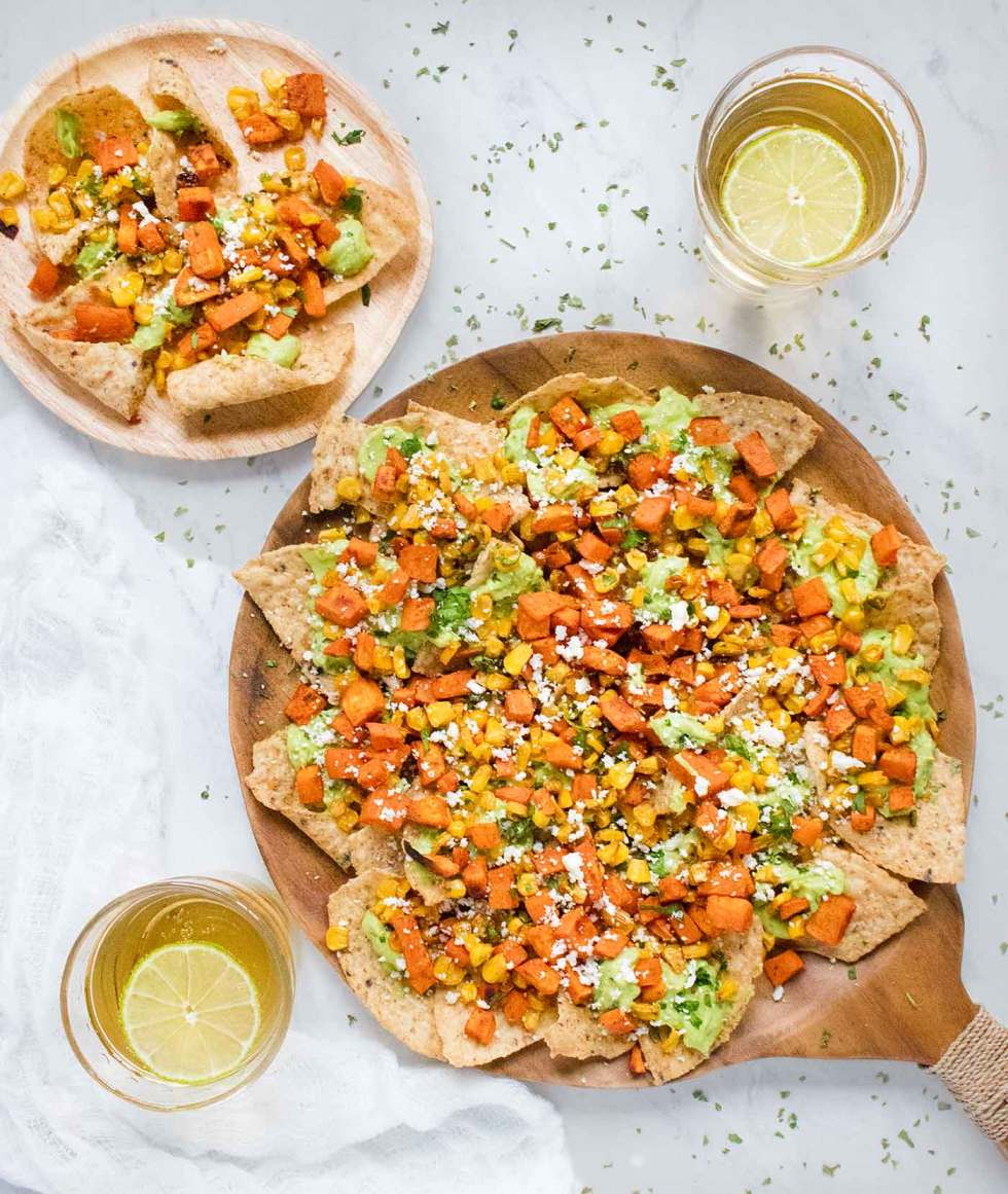 Sweet potato nachos on a plate and on a serving board, with margaritas