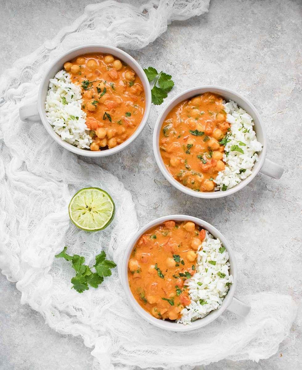 Three bowls of chickpea peanut stew served with cauliflower rice blend