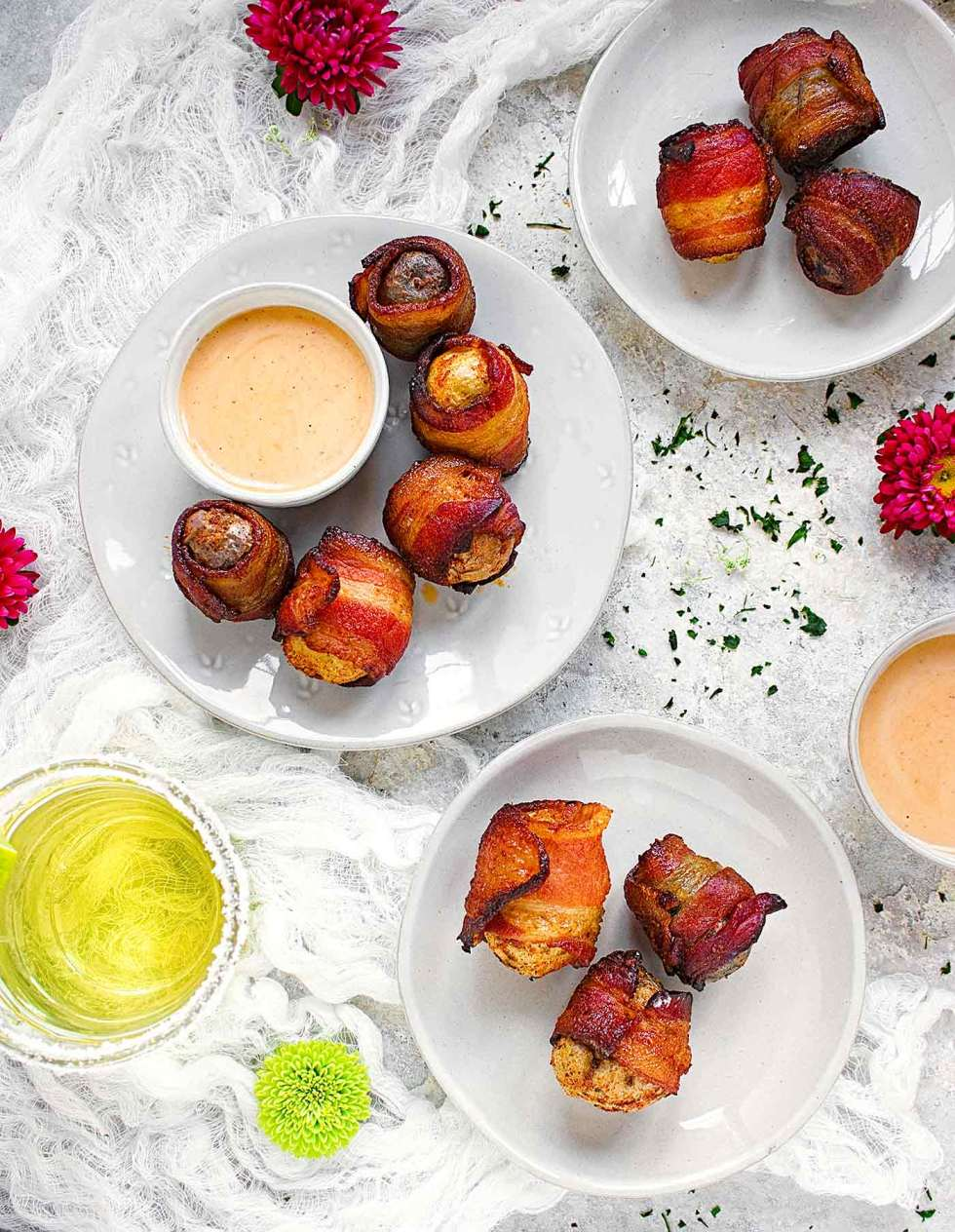 Bacon wrapped potatoes on individual plates with dipping sauce