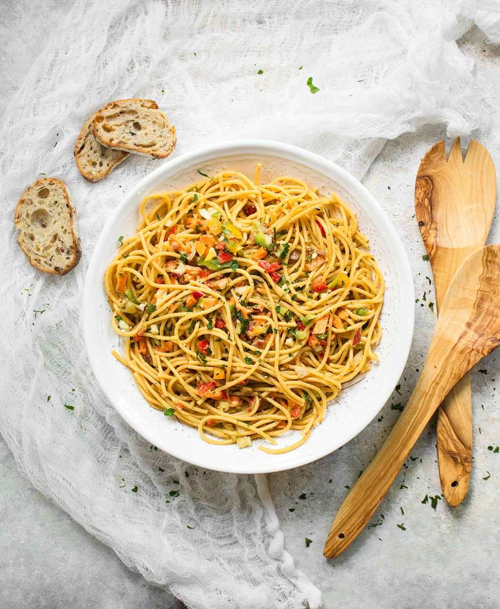 Cold Spaghetti Salad in a big, white serving bowl with wooden serving spoons on the side