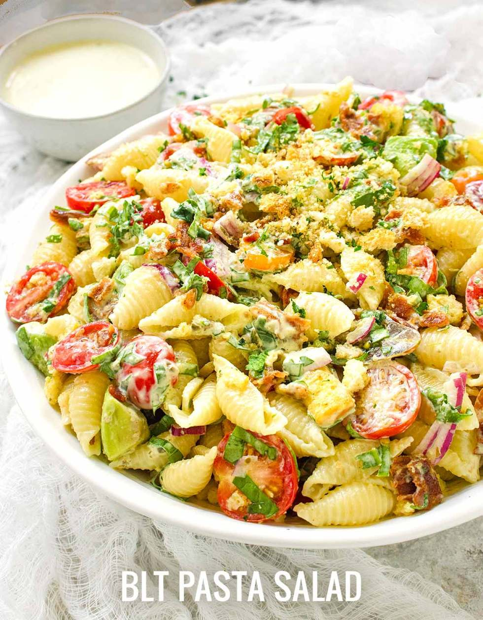 Side view of a big bowl of BLT pasta salad, with a small bowl of extra dressing in the background