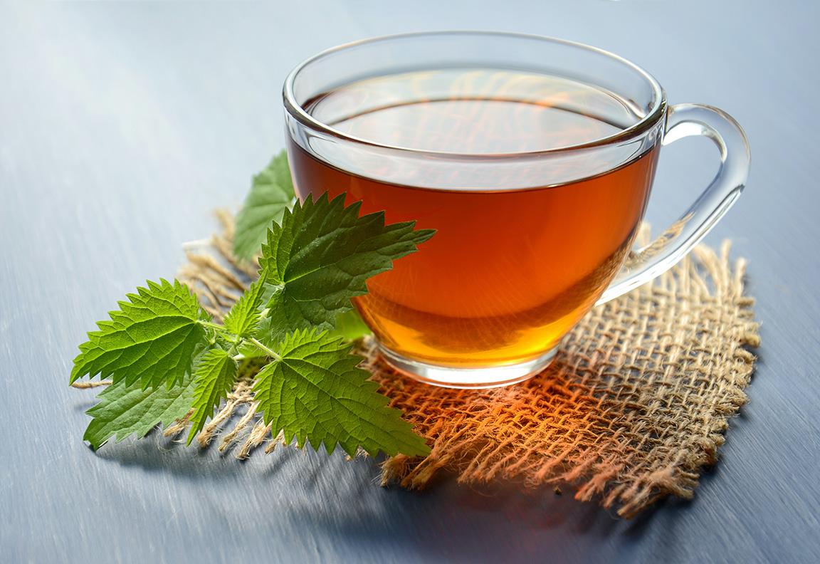 Tee in Glastasse mit frischer Minze auf Juteunterlage
