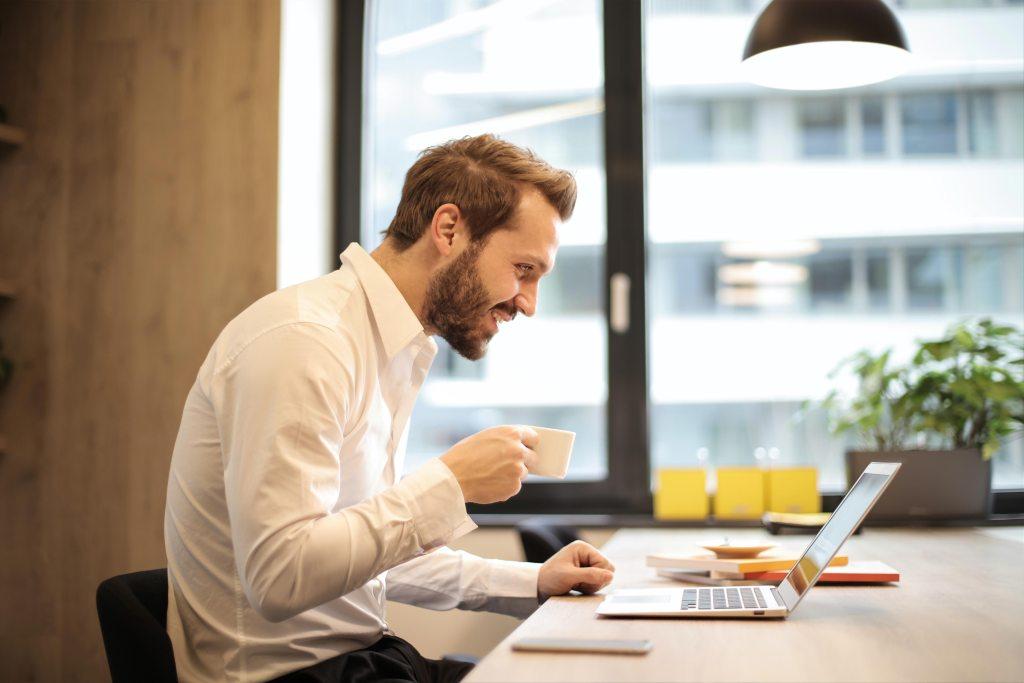 homem a beber café à frente do computador