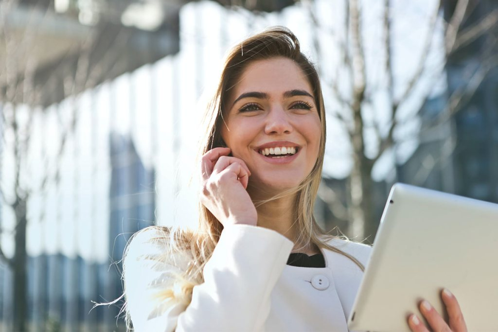 Mulher com tablet a falar pelo telemóvel