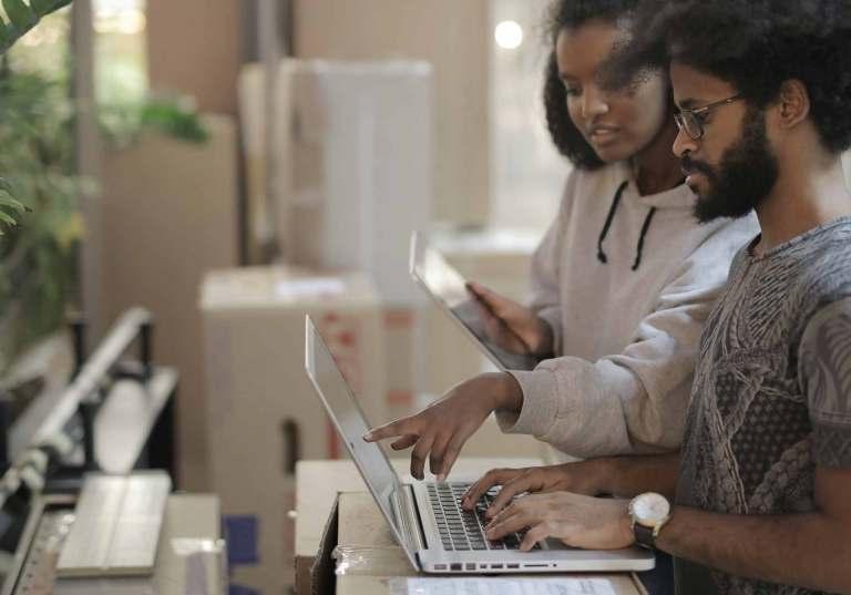 Jovens a usar laptop e tablet num espaço de trabalho