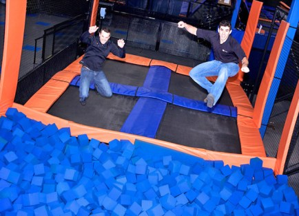 Alumnus Jeff Platt (right) and Barclay Poole, Sky Zone's vice president of marketing & corporate operations, show off their skills in the foam pit at the company's Minneapolis facility. (Courtesy Photo)