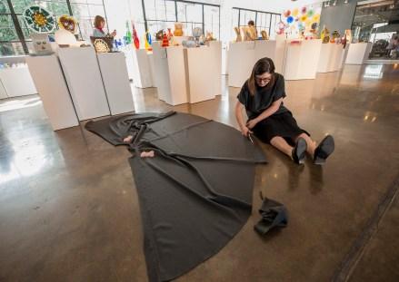 Designer Abbey Maxbauer trims a hemline. (Photo: Joe Angeles/Washington University)