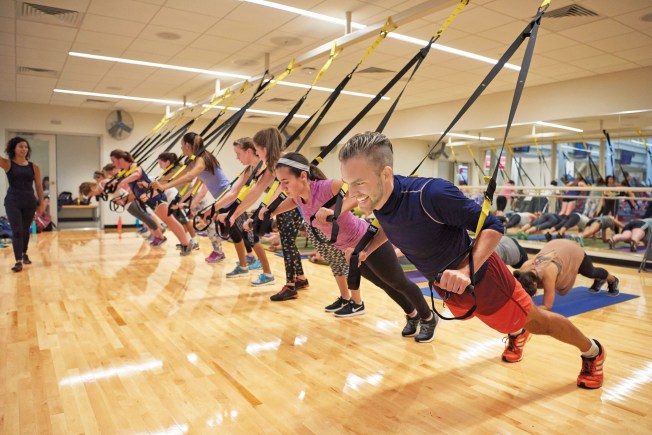 """Sumers offers more than 50 BearFit classes from restorative yoga to Zumba. In """"TRX Butts & Gutts,"""" pictured here, participants use suspension straps and body weight to get anintense workout. (Dan Donovan/Washington University)"""
