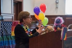 Feldbum speaks in front of rainbow banner