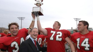 That's a winner! Chancellor Wrighton helps the Bears hoist the Founders Cup after a 2007 victory over the University of Chicago.