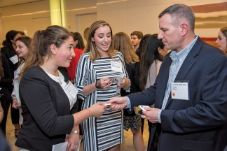 Alumni, parents and current students gathered for networking opportunities at a downtown Washington, D.C., event co-hosted by the WashU Government and Public Policy Network and the WashU Defense, Aerospace and National Security Network last summer. WashU parent Col. Eric Heist (right), MBA '92, hands his business card to undergraduate engineering students Alaina Fierro (left) and Eden Livingston. (Photo: Andres Alonso)