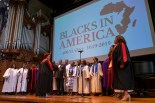 Gospel choir stands while singing on stage with Blacks in America slogan projected behind.