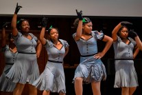 Four young girls dance on stage in grey costumes.