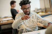 student holds art project