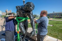 two men install sculpture outside