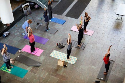 Men and women stand on yoga mats stretching.