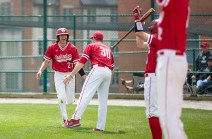 """Auggie Mense high-fives his teammate after scoring a run in a game against Case Western Reserve University in April 2018. """"There is something really special about the way the players support one another. The sense of communities on these teams is amazing."""""""