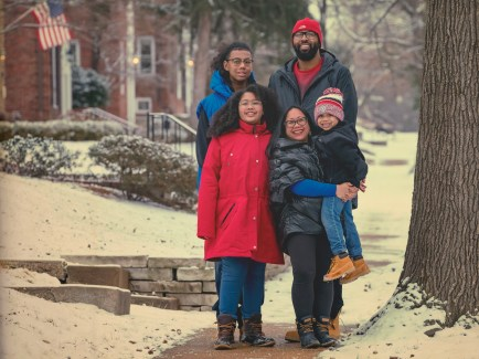 """Sheryl Mauricio (center front), interim director of residential life, lives in Clayton within walking distance of the Danforth Campus with her husband, James Williams, and their three children (from right) JC, 13; Gaby, 9; and Nicco, 4. Before COVID, they were an active family with James as the primary caregiver, navigating school and activities and just dealing with everyday demands of three kids. After COVID, they're still an active family navigating schools and activities with everyday demands, albeit all in one 3-bedroom Clayton duplex. """"It's been crazy,"""" she says, noting that the family has opted for the kids to stay with in-home classes. """"From the beginning we made sure that they each had their own space to work so there could be some transition between work and home."""" For Mauricio, too, that's important. She could work out of an enclosed patio in the warmer months, but winter has brought her inside to the family's dining room table. Her solution: """"I have a lamp on the table, so when that's on, the kids know I'm in a meeting."""" The winter months have been a challenge, but she remains optimistic that when this is all over, there will be a great lesson learned. """"There's so much unknown, and it's really important that we all have grace with each other,"""" she says. """"We need to be kind, be flexible with each other."""" (Photo: Whitney Curtis/Washington University)"""
