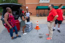 Chancellor Andrew D. Martin (right) visits with a new student and family as they prepare to move in to the South 40 on Aug. 21. (Photo: Joe Angeles/Washington University)