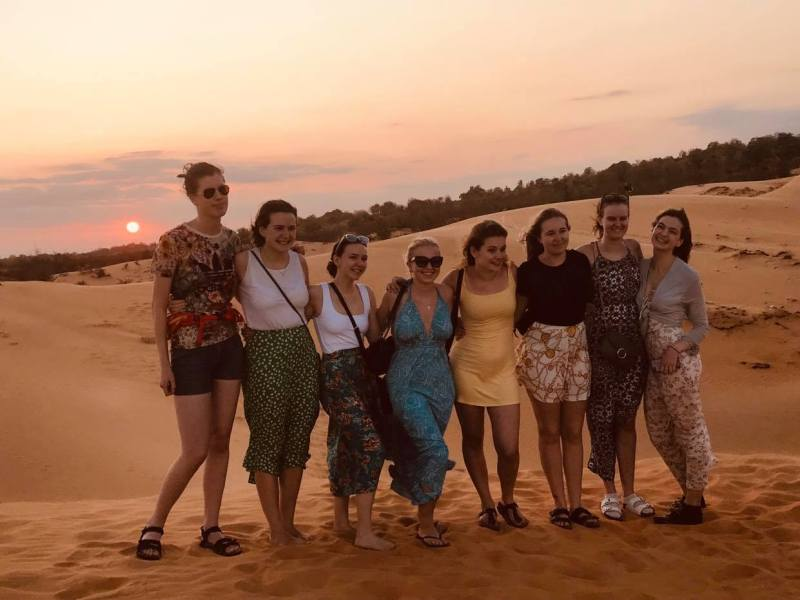 group of students at sunset at the red sandunes