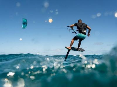 man riding sense foil board with kite