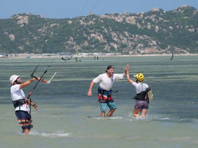 instructor high fiving student with kitesurf equipment