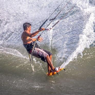 Man kitesurfing in the waves mui ne