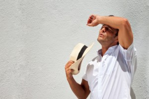 Guy wiping sweat off his forehead during a sunny and hot day
