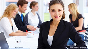 Portrait of a female executive working with others.