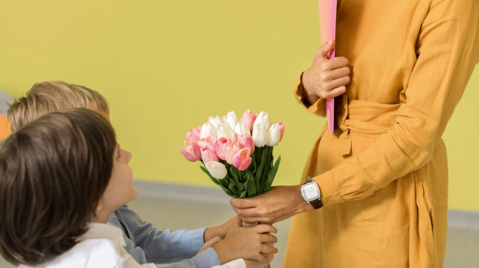 children giving flowers to woman